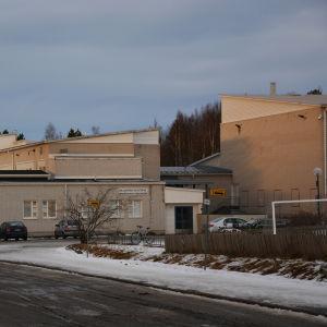 Korsholms högstadium på vårvintern i eftermiddagsljus. En ljus, låg tegelbyggnad.