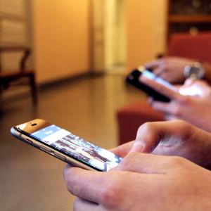 En närbild på ungdomar som surfar på sina smarttelefoner.
