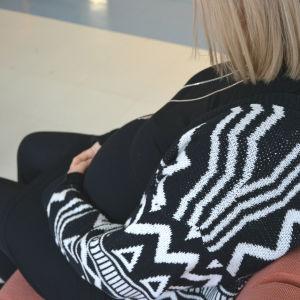 Gravid kvinna sitter på soffa