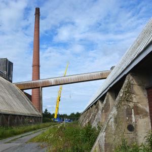 På bilden ser man skorstenen vid sockerfabriken på avstånd. Brevid den står en gul lyftkran. I förgrunden ser man två lagerbyggnader.