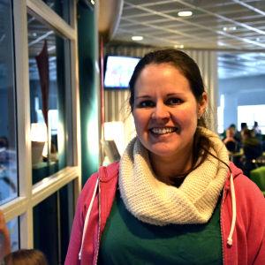 Anna Pensar har en rosa huvtröja på sig och en vit halsduk. Hon står i kaféet i botniahallen med själva springbanan bakom glaset på betraktarens vänstra sida. Anna ler.