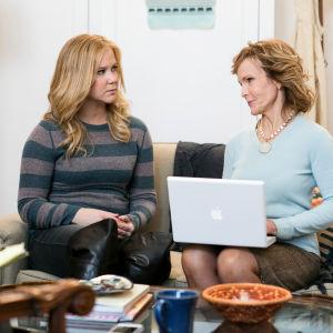 Amy istuu sohvalla äitinsä kanssa.