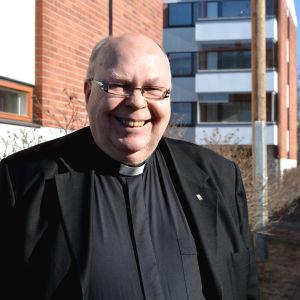 Tor-Erik Store står på trottoaren och tittar in i kameran. Han är prästklädd.