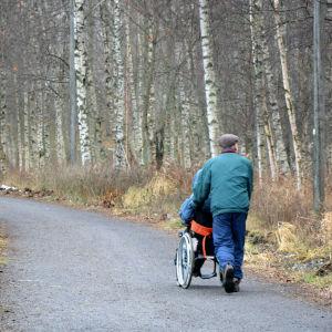 En äldre man kör en person i rullstol längs promenadstråket runt Metviken i Vasa