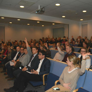 Folk sitter i ett auditorium och vissa markerar med handen.