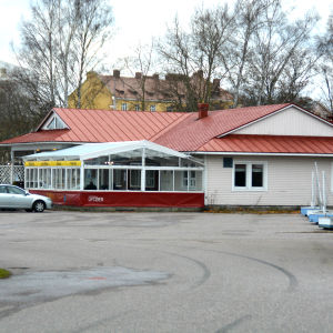 En byggnad med bilar parkerade framför.