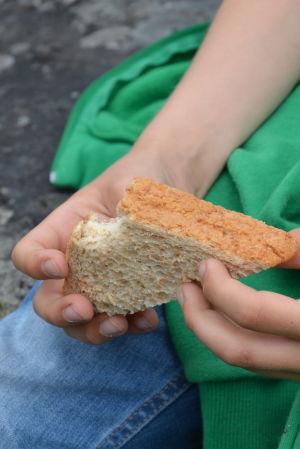 Pojke håller en smörgås i handen.