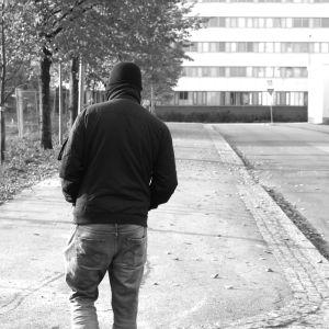 svartvit bild på man bakifrån som går längs gata