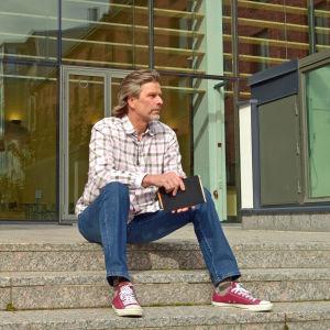 Dekanus Petri Salo sitter på trapporna till Åbo Akademi i Vasa.