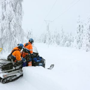 Två personer på en motorkälke i snöig skog.