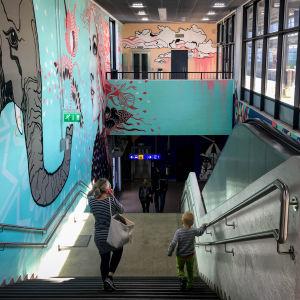 Myyrmäen juna-asemalla seinämaalaus, jossa norsu ja tyttö, portaissa kulkee nainen ja poika selin kameraan.
