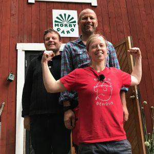 Michael Björklund och Matias Jungar tillsammans med Anna Alm framför en röd träbyggnad.