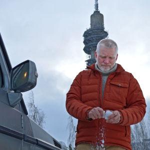 Pata Degerman kramar en snöboll i handen, framför sin terrängbil.