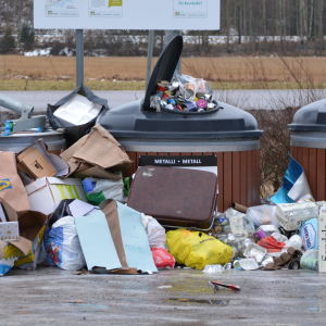 Stora avfallsbehållare för papper, kartong och metall med en massa skräp utanför.