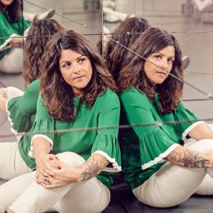 Petra sitter vid en spegelvägg.