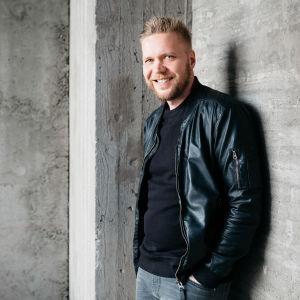 Antti Hirvonen seisoo betoniseinän edessä.