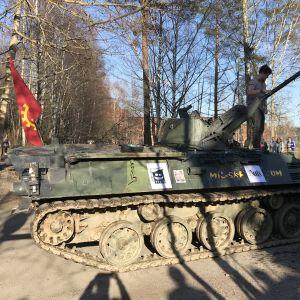 En pansarvagn med en röd flagga och en studerande på.