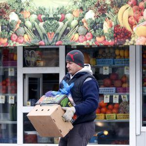 Grönsakshandlare i Moskva bär grönsakslåda.