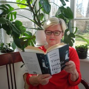 Kirjabloggaaja Airi Vilhunen lukee Kauko Röyhkä kirjaa.