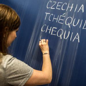 Tjeckisk lärare skriver de föreslagna nya kortformerna på engelska, franska och spanska för Tjeckien.