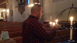 Den intervjuade asylsökanden tänder ett ljus i kyrkan.