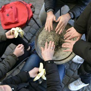 Papperslösa värmer sina händer på Järnvägstorget i Helsingfors.