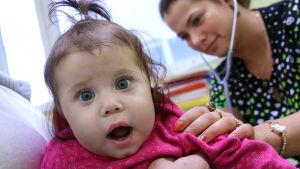 En flicka ser förvånad ut när läkaren lyssnar på hennes lungor på ryggen