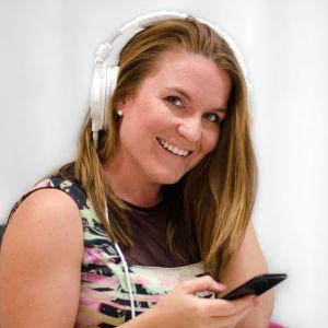 Amie Borgar i en stol lyssnandes i hörlurar.