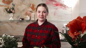 Sanna Mander lagar blommor i en vas i sitt kök.