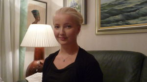 Michelle Gustafsson sitter i en soffa i sitt hem. Tavlor och bordslampa i bakgrunden. Kväll