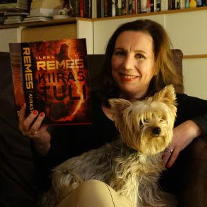 Kirjabloggaaja Kirsi Ranin koiran ja kirjan kanssa nojatuolissa