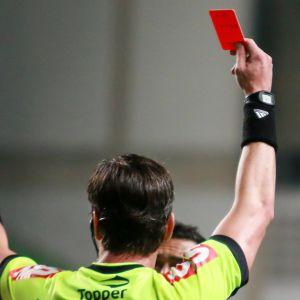 En domare ger rött kort och pekar.