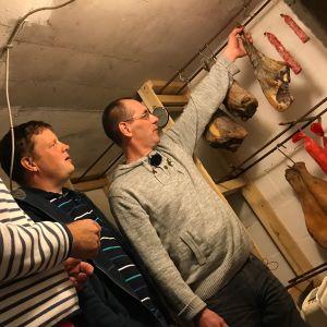 Matias Jungar, Michael Björklund och Pontus Berglund står nere i en källare och betraktar olika köttprodukter som hänger i band vid en vägg.