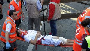 Man som skadats i tjurrusning bärs bort på bår.