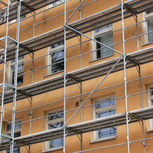 Byggarbetare tar sig upp på byggställningar.