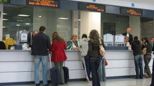 Matkustajia rautatieaseman lipunmyyntitiskillä ja jonossa Espanjassa.