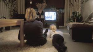 Nainen ja lapsi katsovat televisiota olohuoneen lattialla. Kuva otettu vuonna 1983.