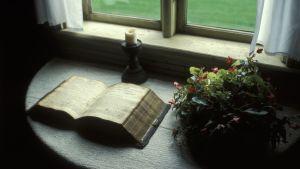 Aleksis Kiven raamattu ja kynttilä pöydällä