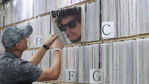En man tar fram en Bob Dylan-skiva från en hylla med massor av lp-skivor.