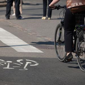 En dam cyklar på sommaren i en stad längs en lättrafikled som korsar en gata.