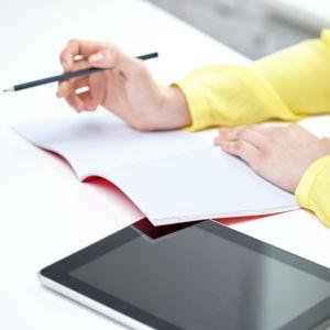 Kvinna skriver i ett anteckningsblock.