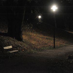 Tom parkbänk i mörker.