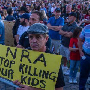 """En man demonstrerar mot vapenlobbyn NRA (National Rifle Association) under minnesstunden för dödsoffren i Parkland, Florida på torsdag kväll. """"NRA sluta döda våra barn"""" står det på plakatet."""