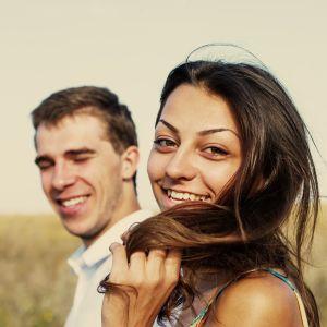 Bild på glad kvinna i förgrunden och glad man bakom henne