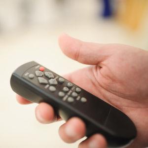 En hand håller i en fjärrkontroll.
