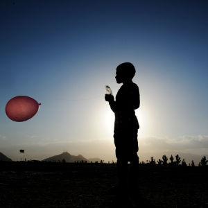Afghansk pojke leker med en ballong i Kabul i juli 2016.