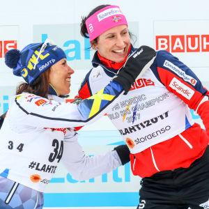 Charlotte Kalla i vitt kramar om Marit Björgen i rött.