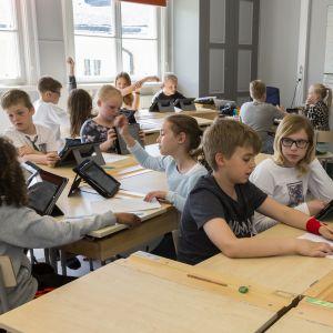 Elever jobbar vid sina pulpeter i klassrummet.