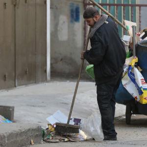 Palestinsk UNRWA-medarbetare sopar gatan i ett flyktingläger nära Nablus på Västbanken.