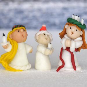 Tre plastfigurer som föreställer en lucia med krona, en tomte och en tärna står på en vit bakgrund.